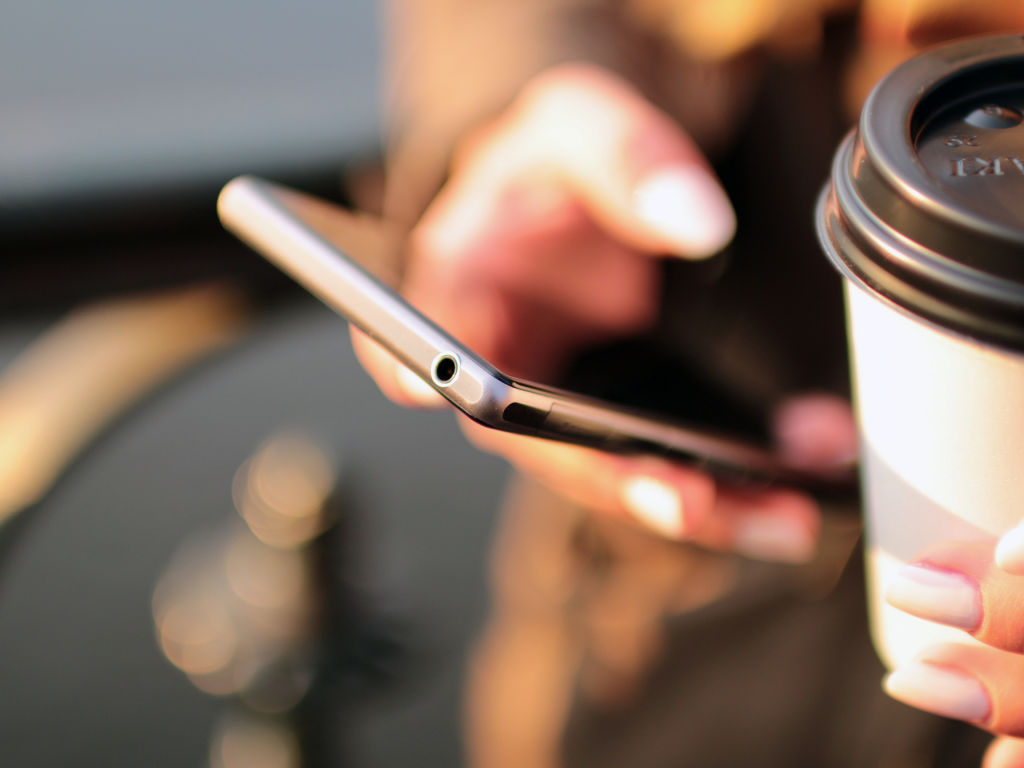 Person holding a phone and coffee